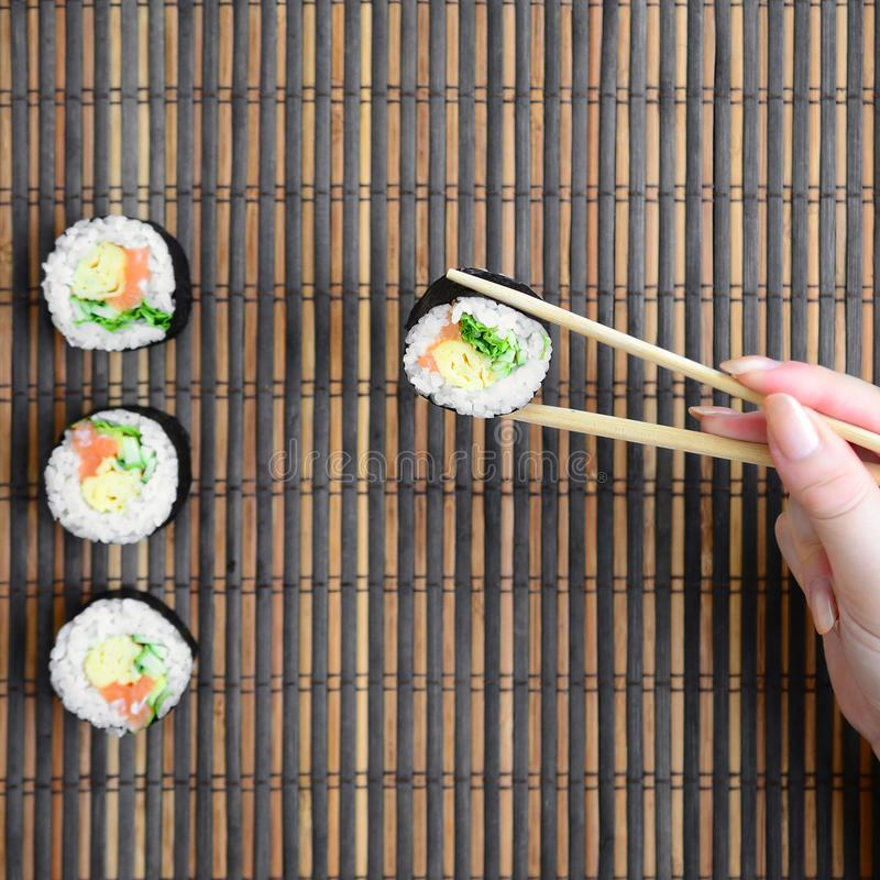 A hand with chopsticks holds a sushi roll on a bamboo straw serwing mat background. Traditional Asian food stock photo