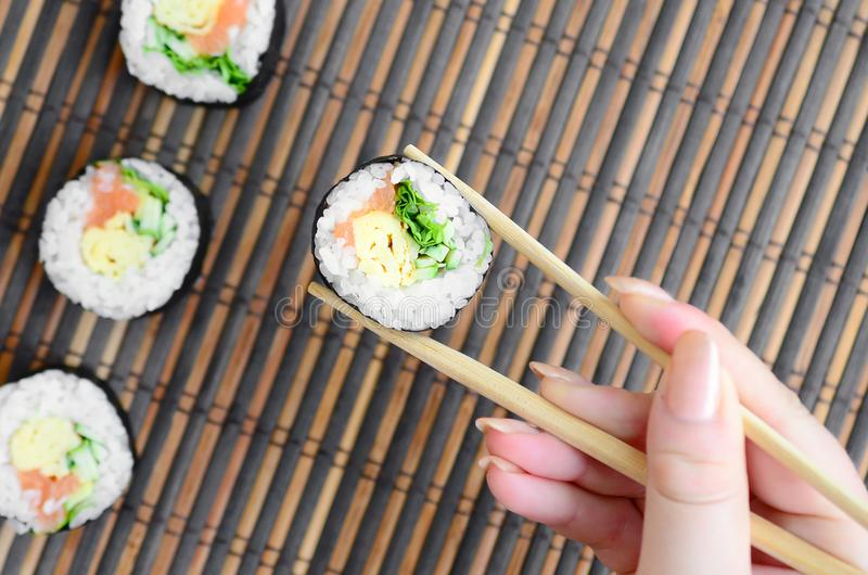 A hand with chopsticks holds a sushi roll on a bamboo straw serwing mat background. Traditional Asian food stock photos