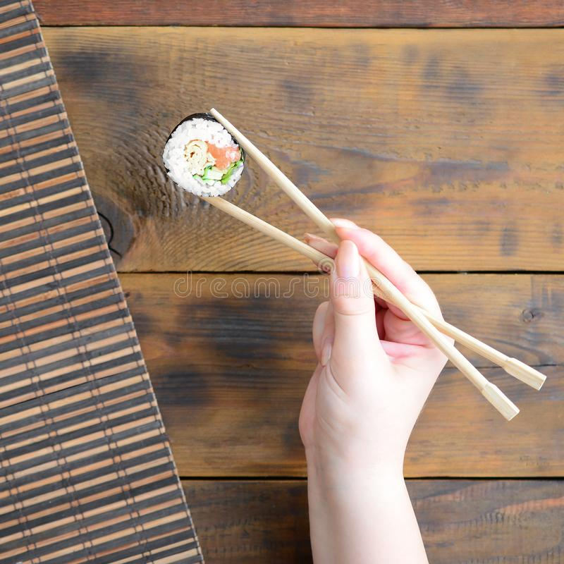 A hand with chopsticks holds a sushi roll on a bamboo straw serwing mat background. Traditional Asian food stock image