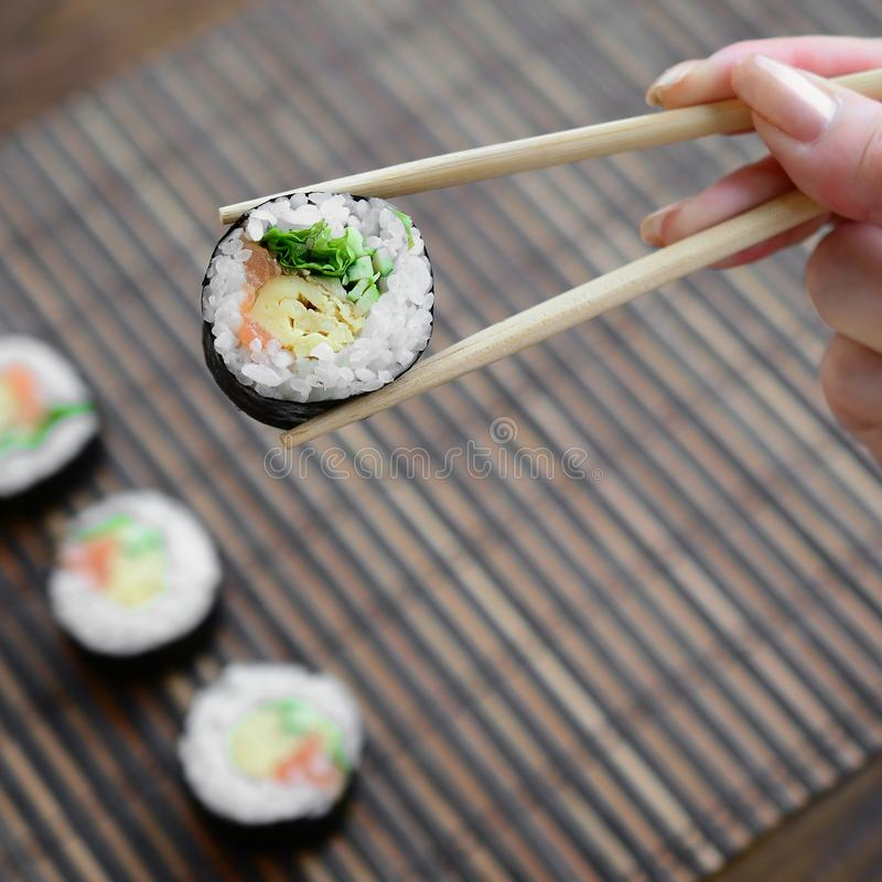 A hand with chopsticks holds a sushi roll on a bamboo straw serwing mat background. Traditional Asian food royalty free stock photo