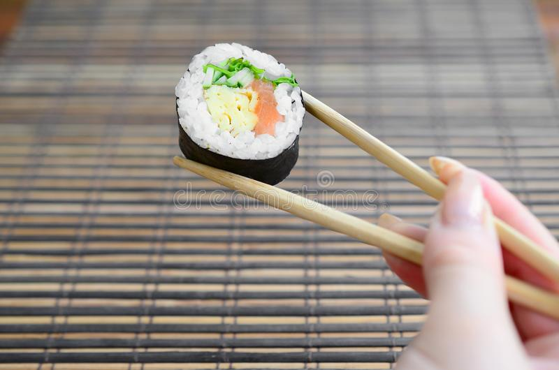 A hand with chopsticks holds a sushi roll on a bamboo straw serwing mat background. Traditional Asian food royalty free stock photography