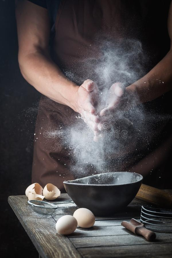 Hand clap of chef with flour. Hand clap of professional chef with bowl for cooking and baking utensils with splash flour on dark background stock image