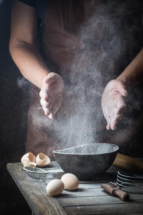 Hand clap of chef with flour. Hand clap of professional chef with bowl for cooking and baking utensils with splash flour on dark background stock photography