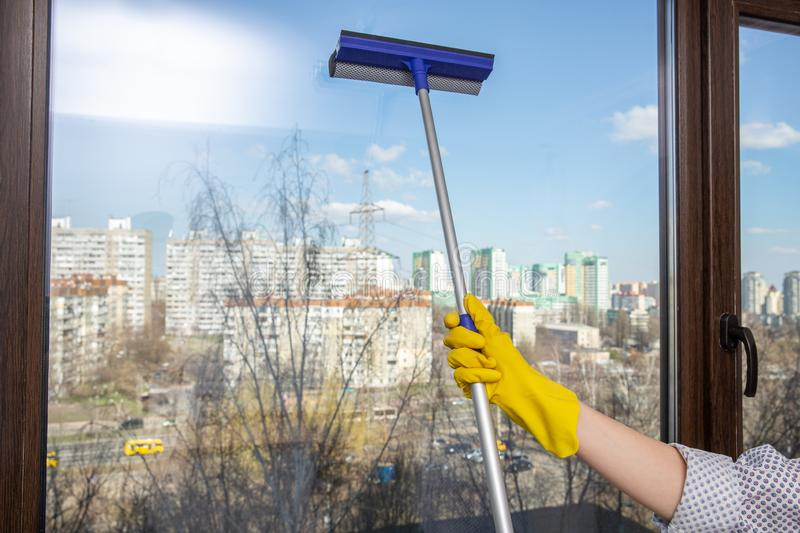 Hand cleaning glass window. A female hands in bright yellow gloves washes the windows stock photography