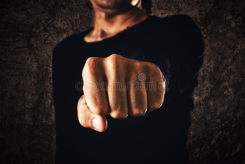 Hand with clenched fist. On dark background. Power, determination, resistance concept stock image
