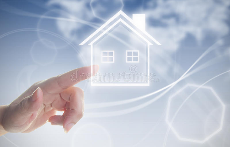 Hand clicking on house symbol. Finger pressing touch screen interface with house real estate symbol stock photo