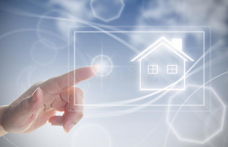Hand clicking on house symbol. Finger pressing touch screen interface with house real estate symbol royalty free stock photo