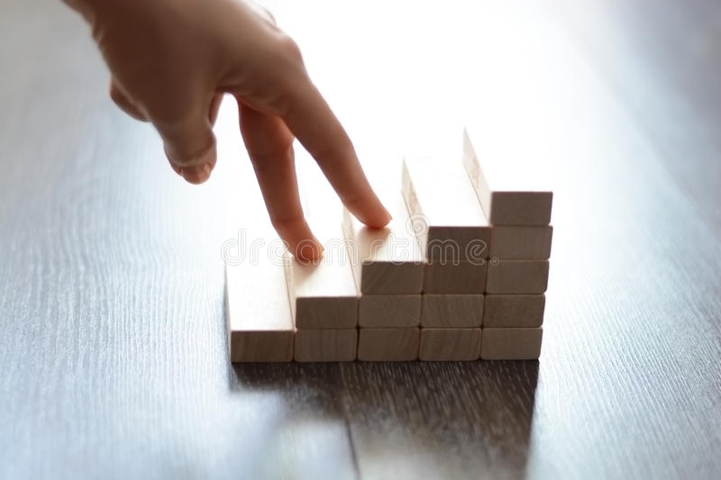 Hand climbing stairs made by wooden blocks. Fingers climbing stairs made by wooden blocks symbolizing career ascendance royalty free stock photography