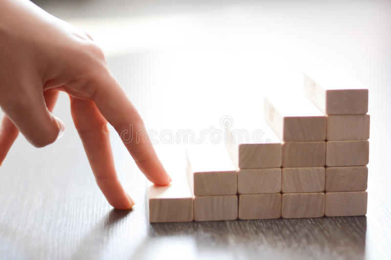 Hand climbing stairs made by wooden blocks royalty free stock photography
