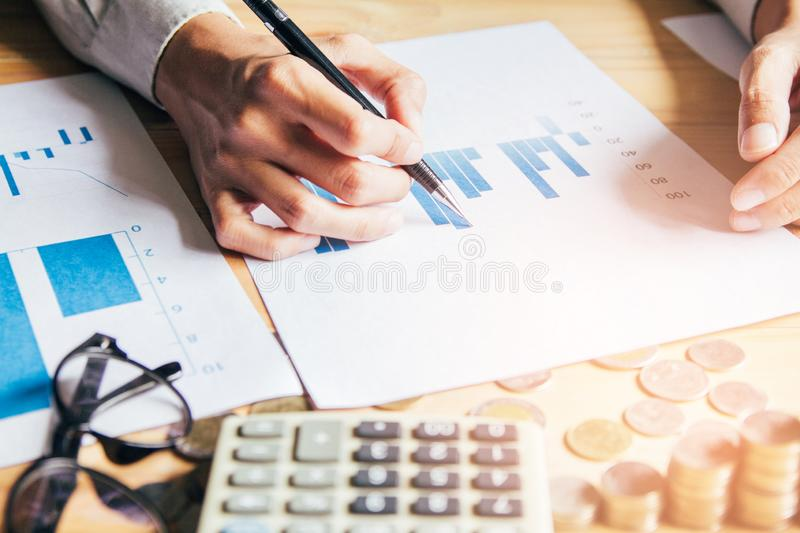 Hand close up,writing report and Calculating finances and calculate on table at home office stock images