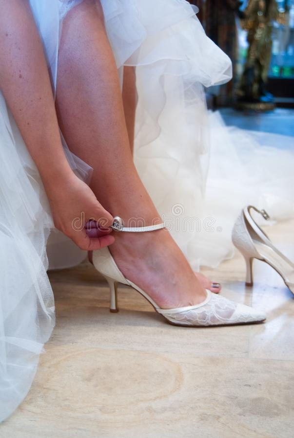 Hand closing shoe. Closeup of a bride,who`s closing her white wedding shoes while preparing royalty free stock photos