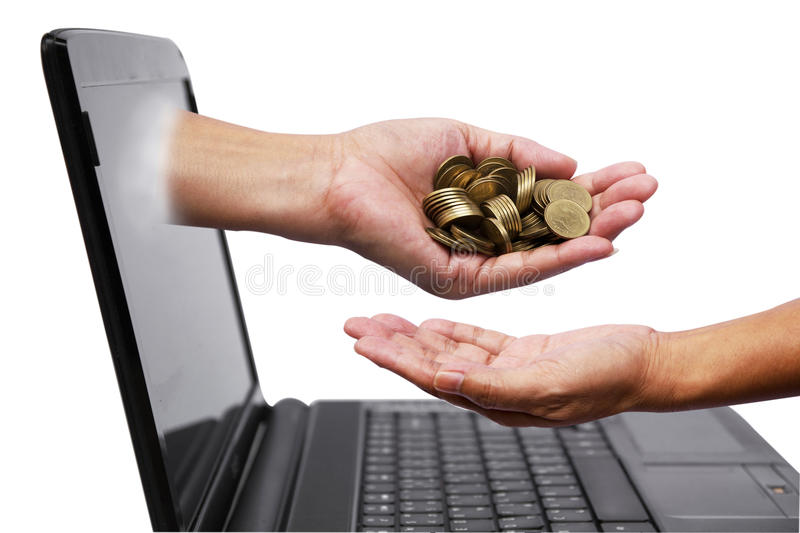 Hand with coins comes out of laptop monitor and pour down coins royalty free stock image