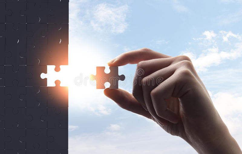 Hand collect puzzle. On a sky background stock photo