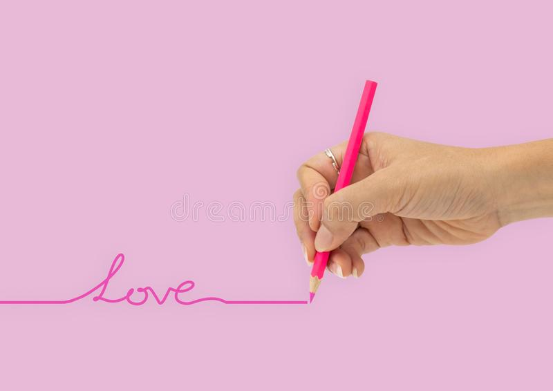 Hand with color pencil is writing love line isolated on pink ba. Ckground stock photos