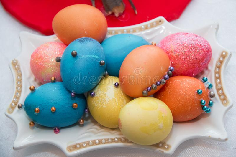Hand colored Easter eggs on vintage plate.Many Colorful Easter Eggs On White Plate Placed By Heap and marble background . Image of royalty free stock photography