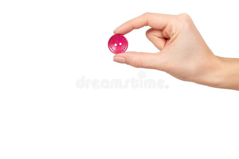 Hand with colorful sewing button, decoration accessory. Isolated on white background. Copy space template, clothing, design, fashion, object, textile, red royalty free stock photography