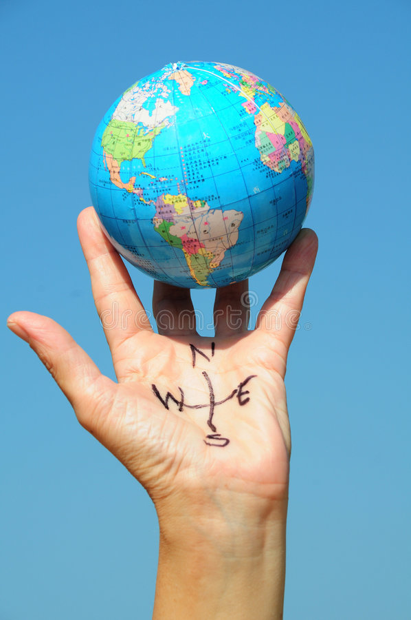 Hand Compass with globe. A hand with compass directions written on it and holding a globe royalty free stock images