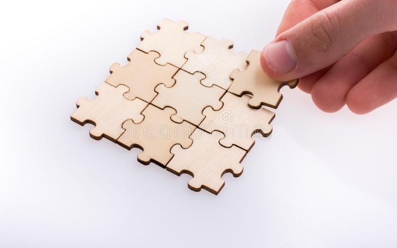 Hand completing a puzzle group on white background stock photo