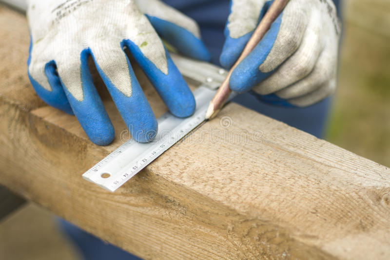 Hand of a construction worker points with a pencil the distance on a wooden edge. royalty free stock images