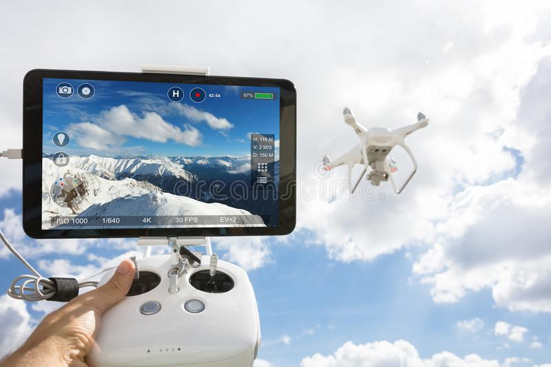 Hand controlling drone filming snowcapped mountains stock photography