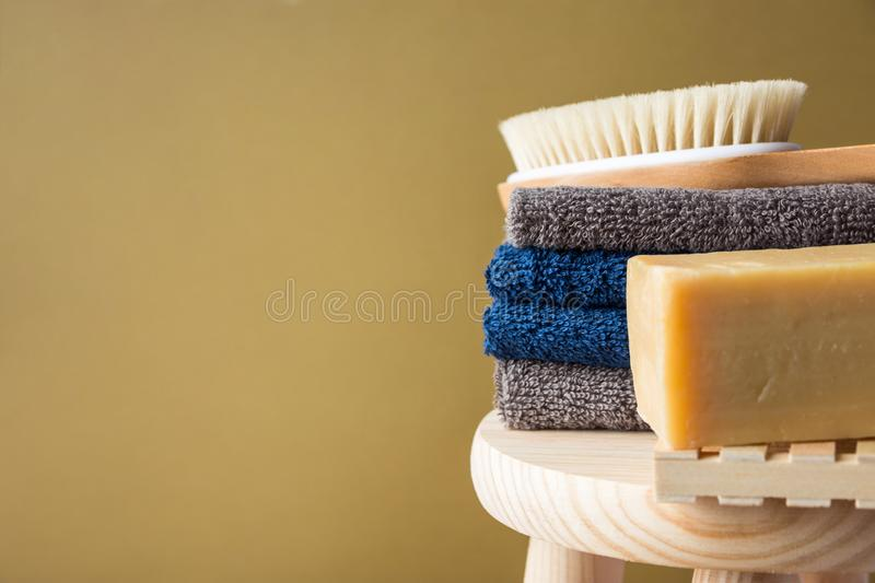 Hand crafted artisan olive oil soap body brush folded cotton towels stacked on wooden chair painted beige wall background. Spa. Wellness skin care organic stock image