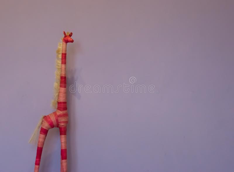 Hand crafted giraffe decoration on a purple wall background royalty free stock photography