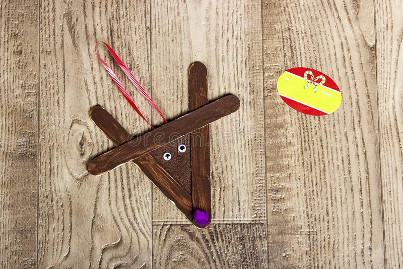 Hand crafted popsicle reindeer, laying on a wood grain background royalty free stock photography