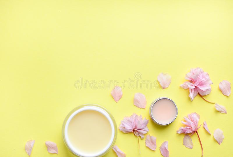 Hand cream, lip balm on a yellow background, flower petals. Space for a text. stock photography