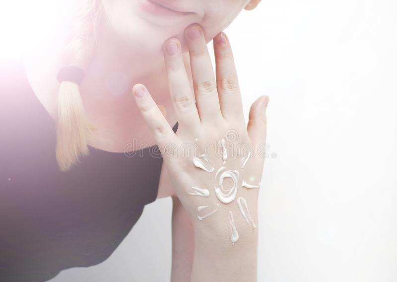 Sunscreen on the hand in the form of a sun and a smile. Hand cream, nourishing cream, personal care, moisturizer stock photos