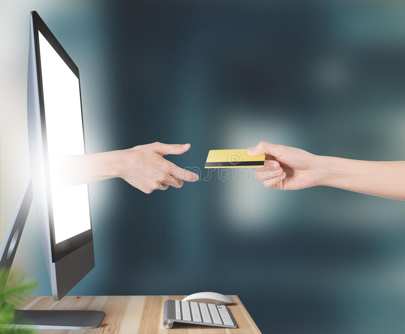 Hand with credit card comes out of monitor stock photography