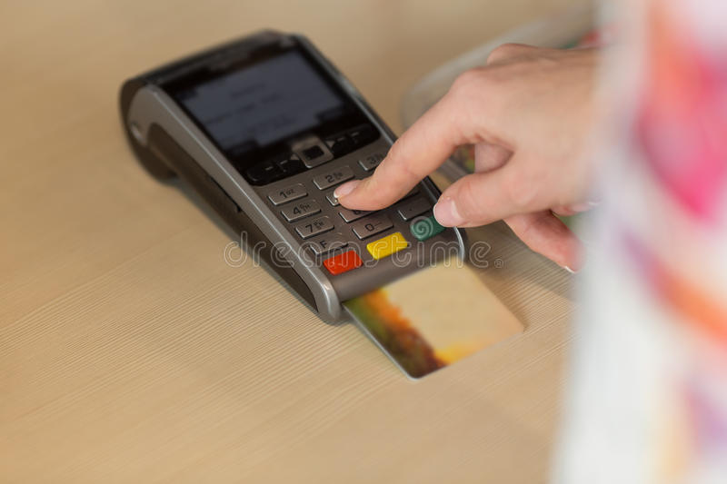 Hand with credit card swipe through terminal for payment in cafe. Close up of hand using credit card swiping machine to pay. Hand with credit card swipe through stock photography