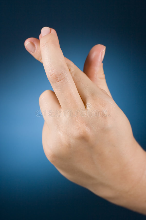 Hand with crossed fingers stock images