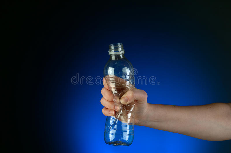 A hand crushing a recyclable plastic bottle. Horizontal image of a hand crushing a recyclable plastic bottle on a blue glow background royalty free stock photography