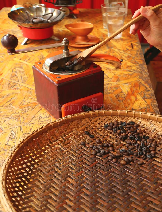 Hand cupping dark roasted coffee beans with wooden spoon into coffee grinder for preparing homemade coffee royalty free stock photos