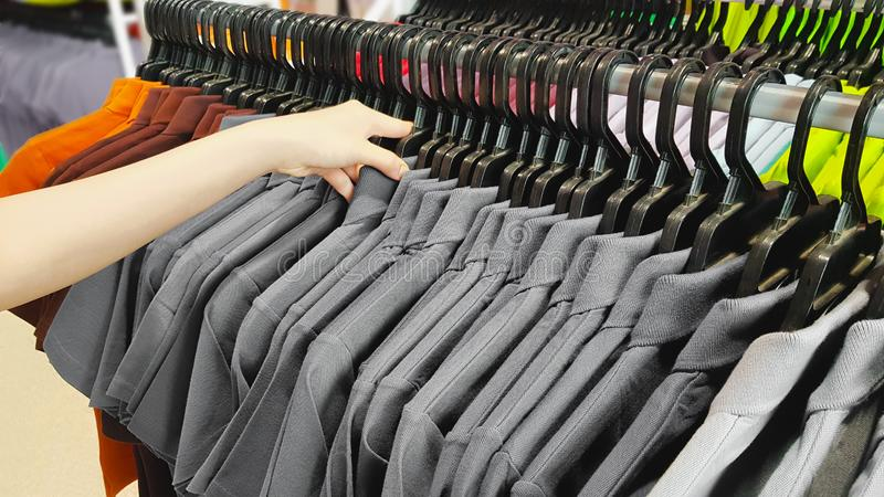 Hand of Customer Choosing Discount Clothes in a Shopping Mall. People Searching or Buying Cheap Cotton Gray T-Shirt on Rack Hanger royalty free stock photo