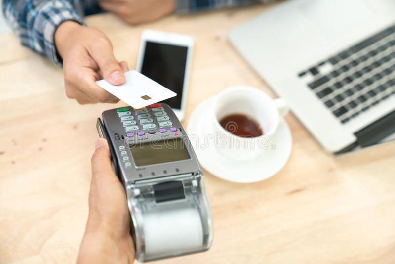 Hand of customer paying with contactless credit card with NFC te. Chnology. Bartender with a credit card reader machine at bar counter with female holding credit stock photo