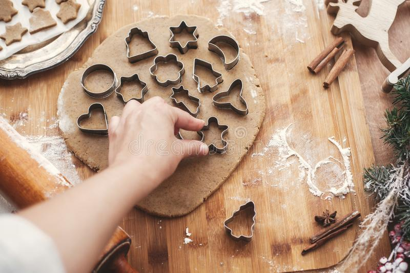 Hand cutting christmas gingerbread cookie man on dough on background of wooden rolling pin, cookies, metal cutters, christmas dec. Orations on rustic table stock photo
