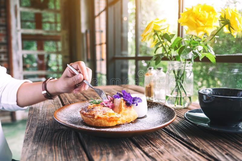 A hand cutting a piece of coconut pie by fork. A hand cutting a piece of coconut pie with a beautiful decoration in a plate to eat by fork stock photo