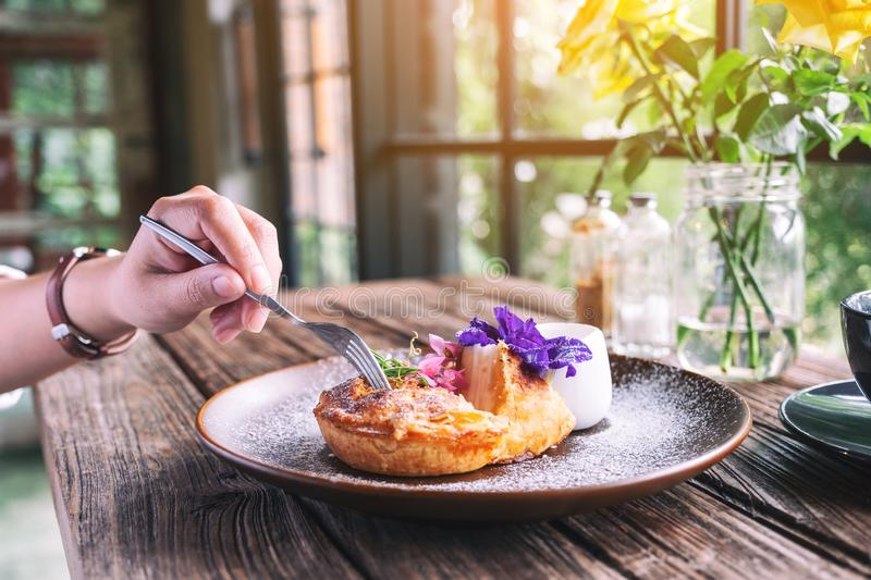 A hand cutting a piece of coconut pie with a beautiful decoration. In a plate to eat by fork stock photography