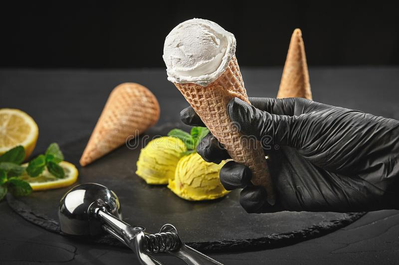 Hand in a dark glove is holding a waffle cone with a creamy ice cream on a background of a lemon sorbet decorated with stock photos