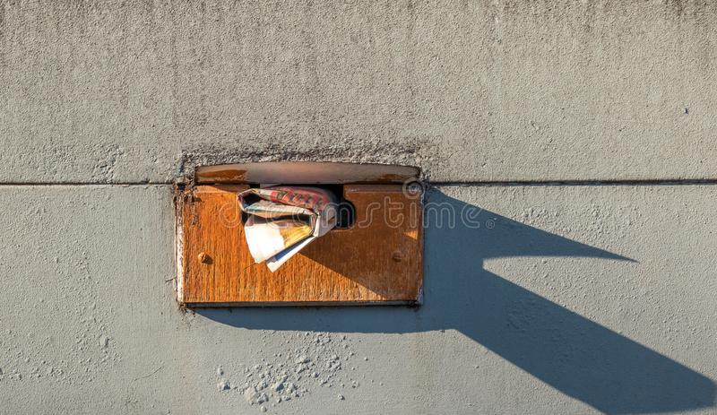 Hand delivered mail in a mailbox. Hand delivered mail sticking out from a weathered mailbox isolated on a dirty wall image with copy space in landscape format royalty free stock images