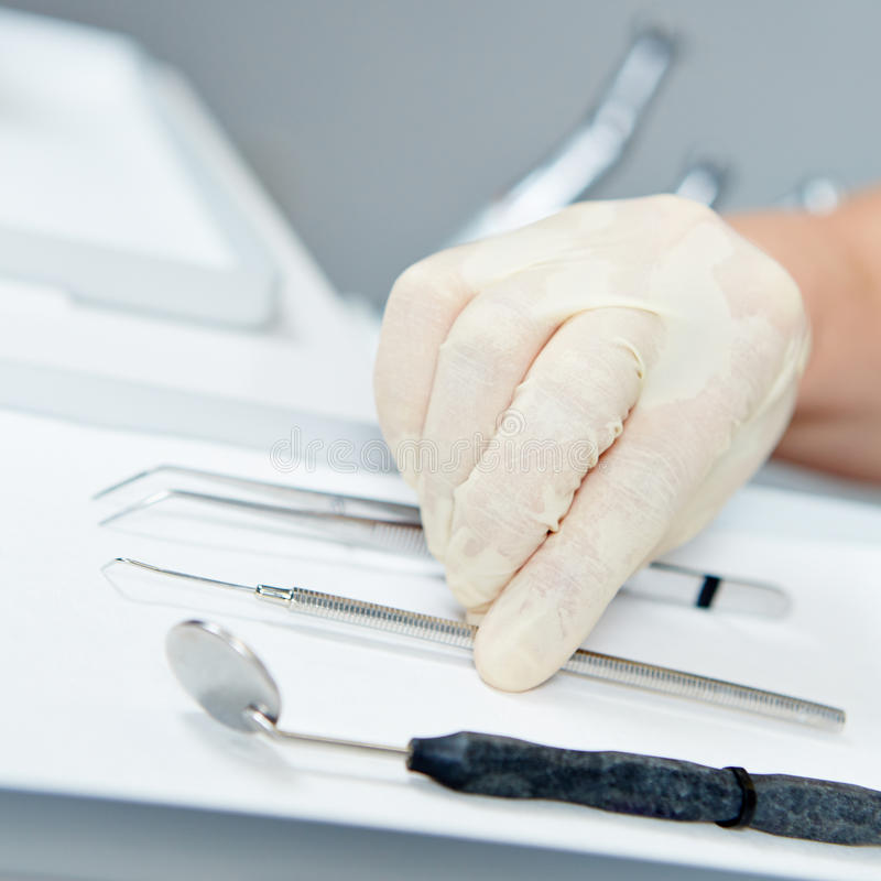 Hand of dentist reaching for probe. For dental examination stock images