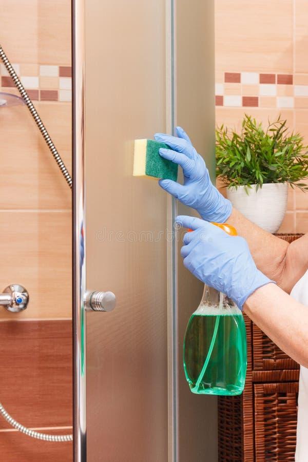 Hand der älteren Frau mit Schwamm und reinigender Reinigungsglasduschtür, Haushaltsaufgabenkonzept stockfoto