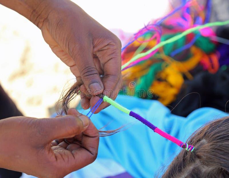 Hand der Afrikanerin verschachtelt das Haar eines kleinen Mädchens mit stockfotos