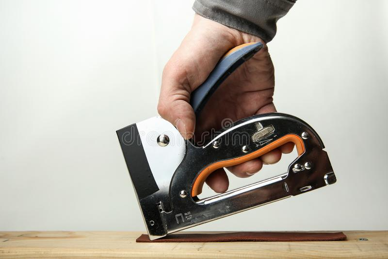 Hand der Arbeitskraft benutzt einen industriellen Stahlhefter lizenzfreies stockfoto