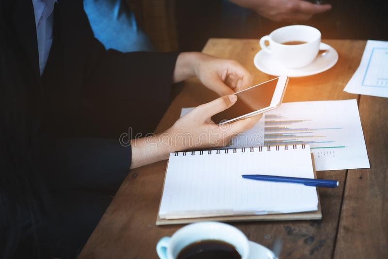 Hand der asiatischen Frau des Geschäfts intelligenten Handykontaktkunden in der Gruppensitzung im Kaffeecafé mit Anmerkungsbuch u stockfotos