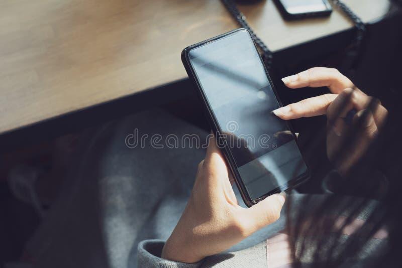 Hand der Frau, die Smartphone auf Holztisch, Raum für Text oder Entwurf verwendet stockbild