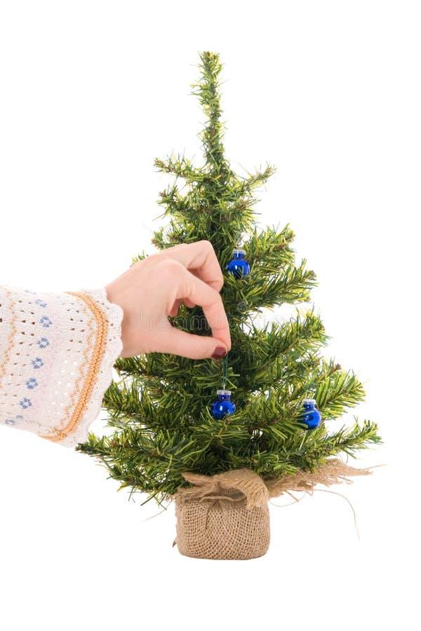 Hand der Frau hängt blaue Weihnachtskugel stockbilder