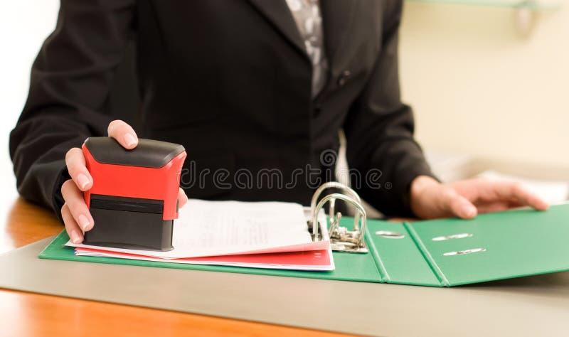 Hand der Frau mit dem Stempeln der Dokumente lizenzfreie stockfotos