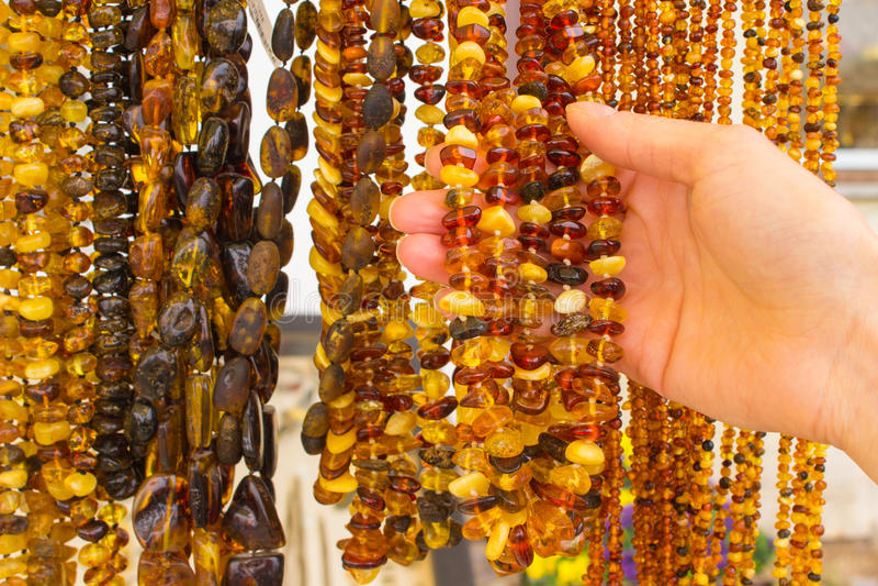 Hand der Frau mit glänzenden fraulichen bernsteinfarbigen Halsketten auf Stall am Basar lizenzfreies stockbild